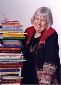 Margaret Read MacDonald stands next to her collection of books she has authered.